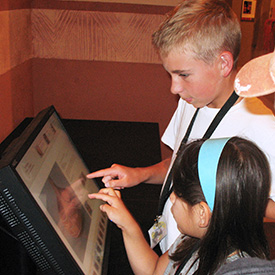 Children interacting with museum kiosk
