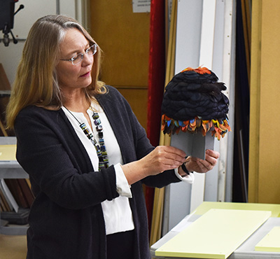 Professor Suzanne Oakdale examines an Amazonian feather hat