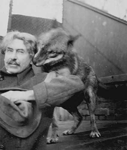Ernest Seton Thompson playing with a wolf