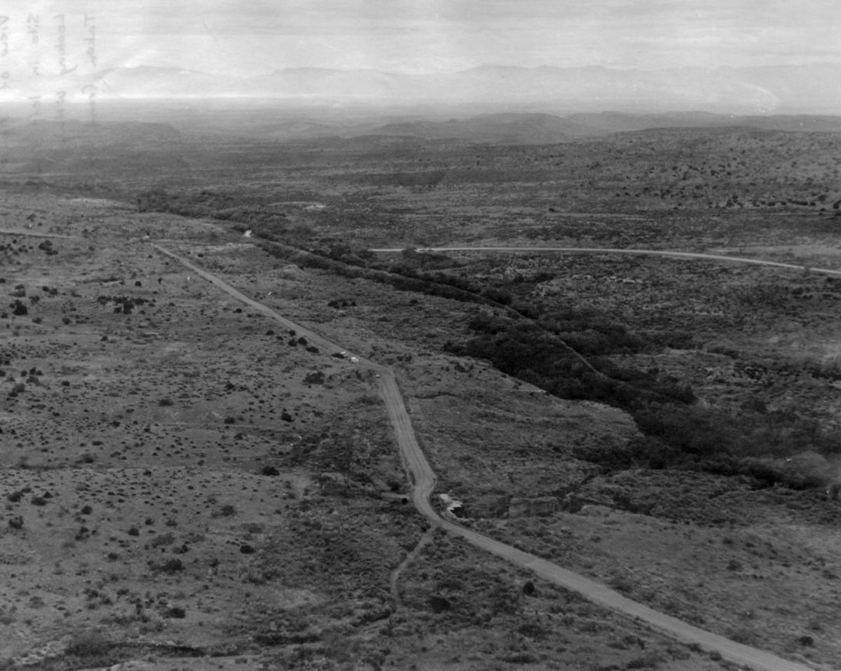 (Figure 2) View of project area from top of Round Mountain, looking west. LA 10832 is located at the bend in Old Mescalero Road in the left center of photo; vehicles are parked at the site.