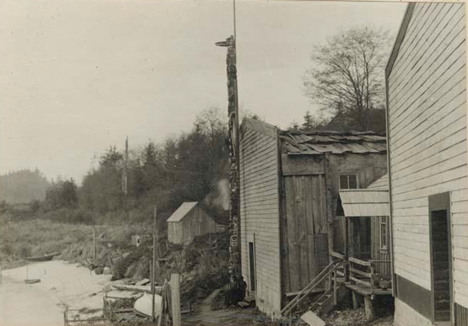 New totem pole; Side view in front of waterfront house, Kalagwees (Qaloǧʷis), 1912